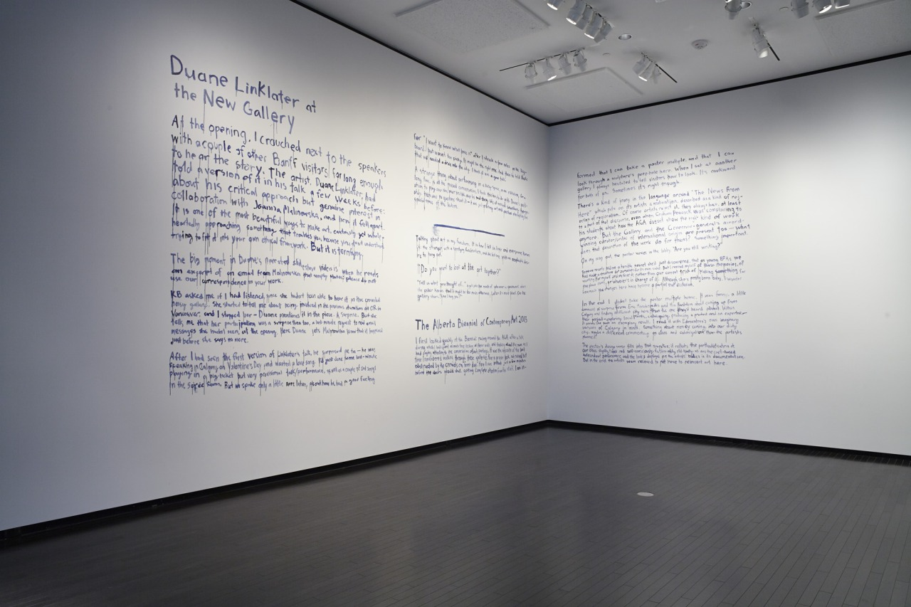 Reviews of Duane Linklater at The New 	Gallery and The Alberta Biennial of Contemporary Art 2013 written in blue paint on 	the wall of the gallery